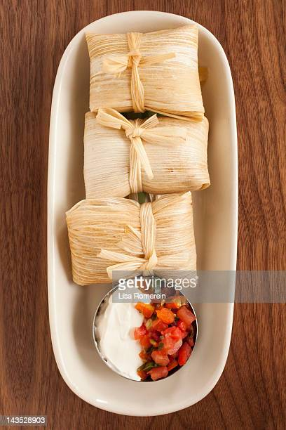 Dish of green corn tamales with sour cream & salsa