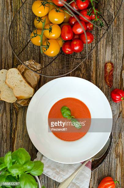 Dish of homemade tomato soup, slices of white bread and tomatoes on wood