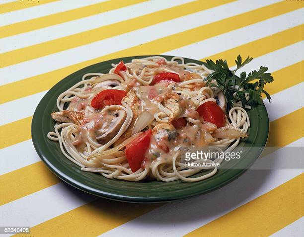 A dish of Italianstyle pasta noodles with a chicken onion mushroom and tomato sauce and parsley sits on a yellow and white striped surface 1970s