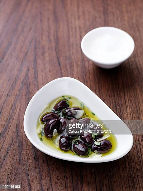 dish of olives in oil - kalamata olive stock photos and pictures