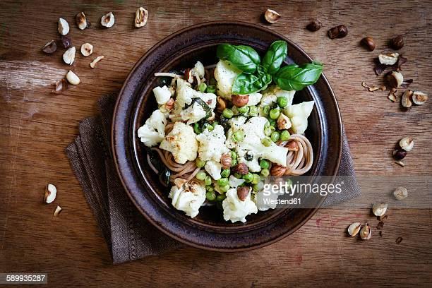 Dish of whole grain spelt spaghetti with roasted cauliflowers, hazelnuts, peas and basil