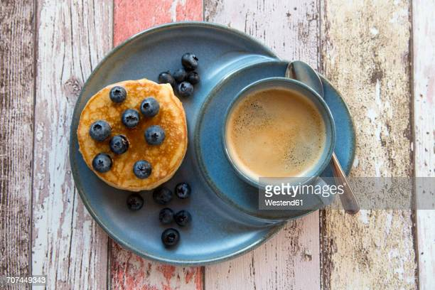 Dish with pancakes, blueberries with maple sirup and a cup of black coffee