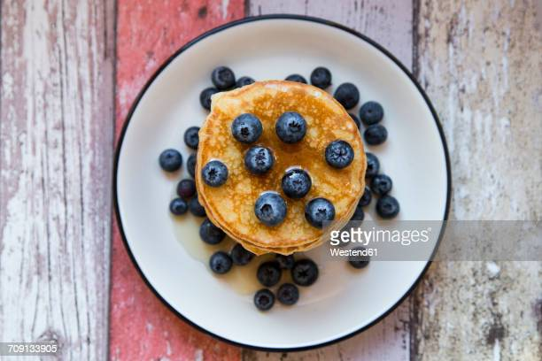 dish with pile of pancakes and blueberries with maple sirup - pancake stock pictures, royalty-free photos & images