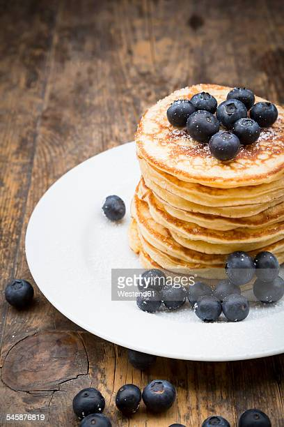 Dish with pile of pancakes, blueberries, sprinkled with icing sugar