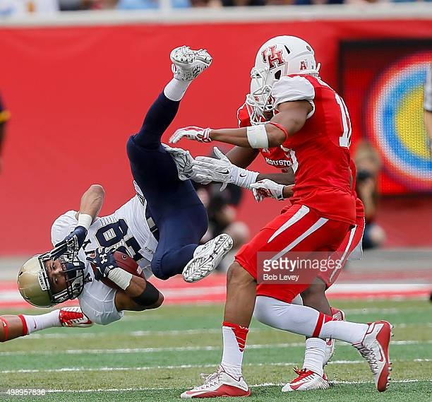 Dishan Romine of the Navy Midshipmen is upended by D'Juan Hines of the Houston Cougars and Adrian McDonald after a catch in the second quarter at...