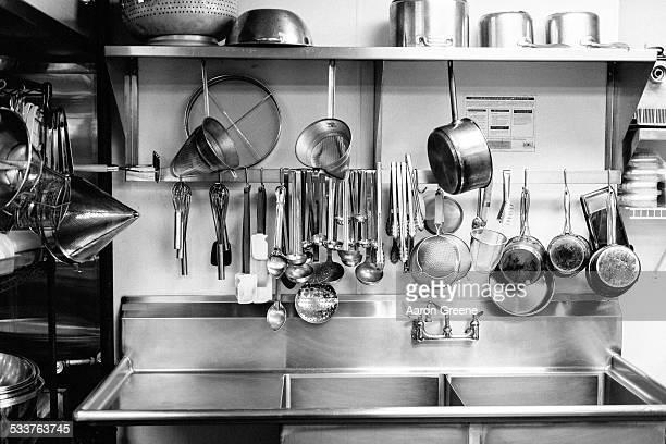 dishes hanging above commercial kitchen sink - pan keukengereedschap stockfoto's en -beelden