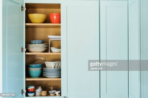 dishes in cupboard - cabinet stock pictures, royalty-free photos & images