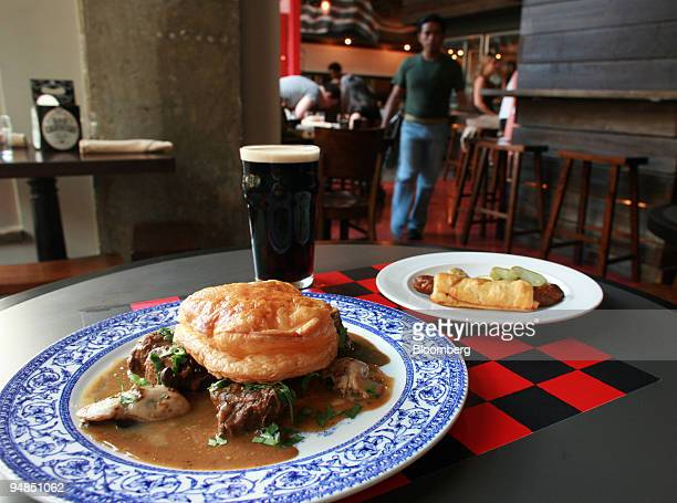 Dishes of 'frog in a puff' front and bangers and mash rear are arranged with a pint of Guinness stout for a photo at CommonWealth a new gastropub in...