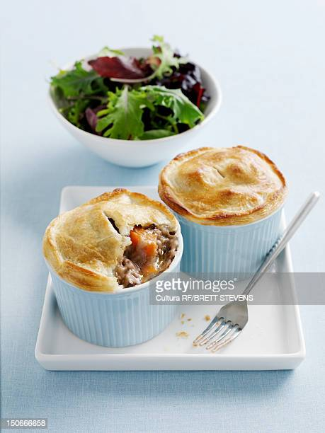 Dishes of mini pot pies with salad