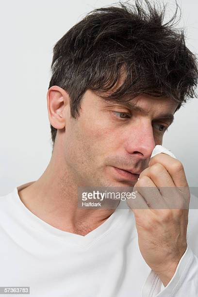A disheveled man wiping his nose