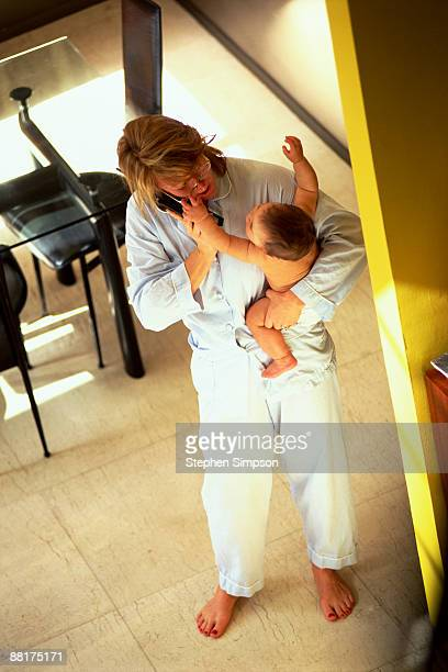 Disheveled mother holding baby and talking on phone