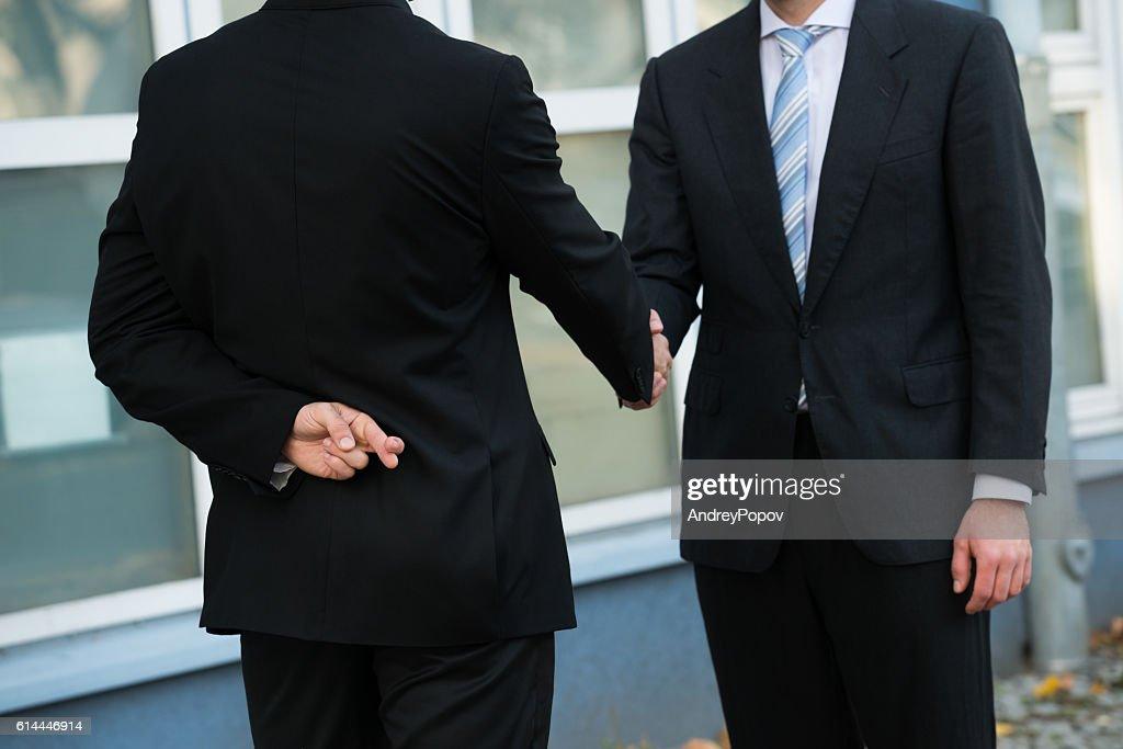 Dishonest Businessman Shaking Hands With Partner : Stock Photo