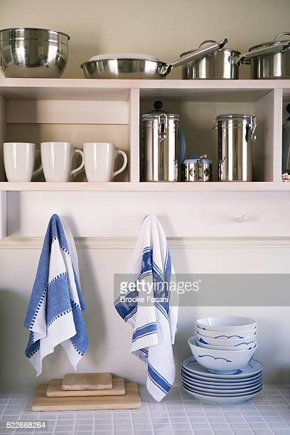 Dishtowels hanging over organized kitchen cupboards