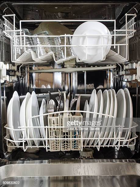 Dishwasher opened in the kitchen with plates and clean glasses