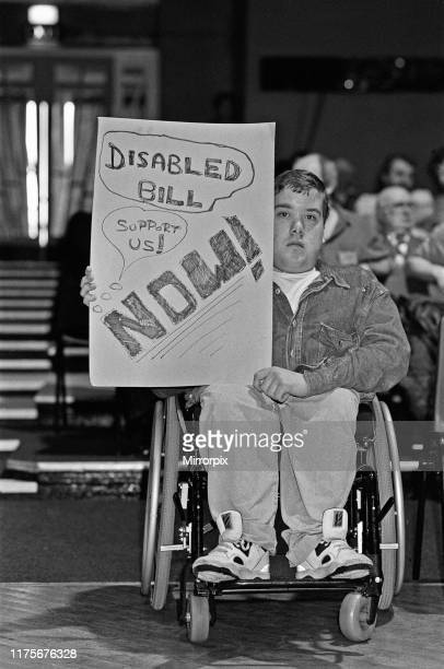 Disibilities civil rights protester holds a placard campaigning for a Disability Discrimination bill during Tony Blairs speech to the North West...
