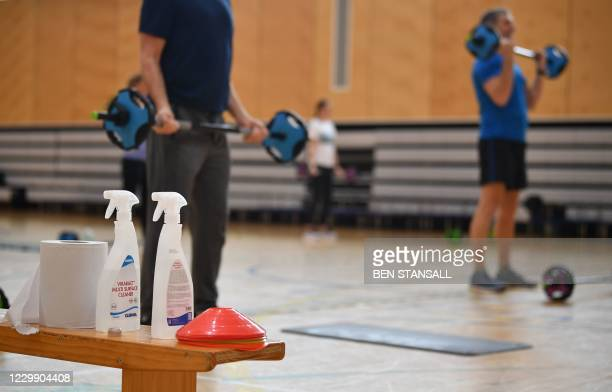 Disinfectant and handtowels are seen as gym users take part in a socially distanced weights class at Kensington Leisure Centre in London on December...