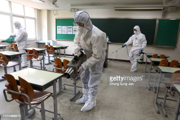 Disinfection professional and government official wearing protective clothing spray antiseptic solution at classroom to prevent the spread of the...
