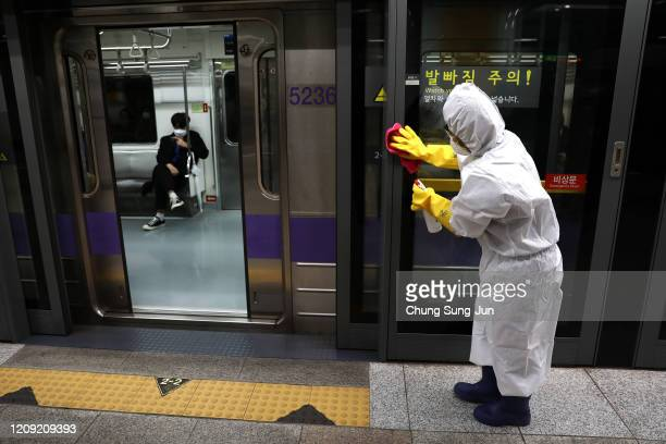 A disinfection professional wearing protective gear spray antiseptic solution against the coronavirus at a sybway station on February 28 2020 in...