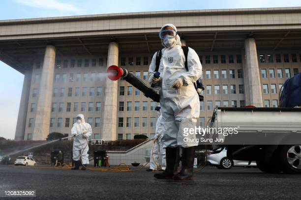 Disinfection professionals wear protective gear spray anti-septic solution against the coronavirus at a National Assembly on February 24, 2020 in...