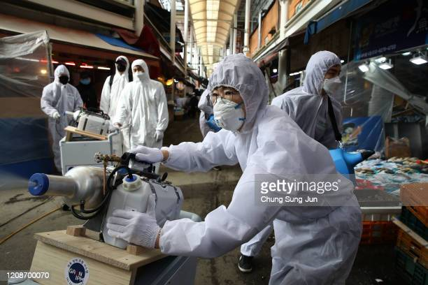 Disinfection professionals wearing protective gear spray antiseptic solution against the coronavirus at a traditional market on February 26 2020 in...