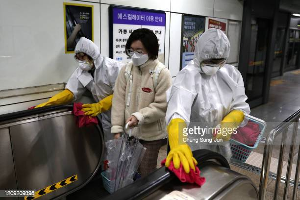 Disinfection professionals wearing protective gear spray antiseptic solution against the coronavirus at a sybway station on February 28 2020 in Seoul...