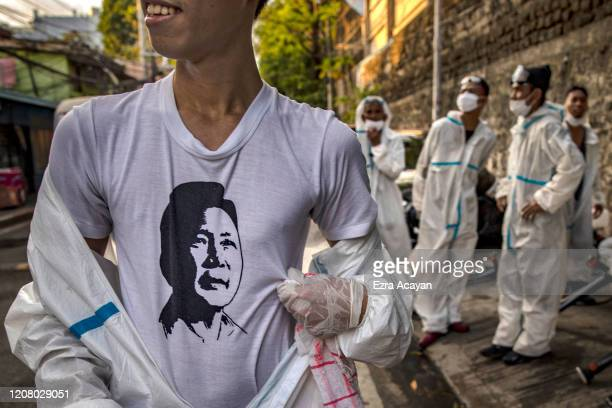 A disinfection worker is seen wearing a shirt with a portrait of former Philippine dictator Ferdinand Marcos while taking a break on March 23 2020 in...