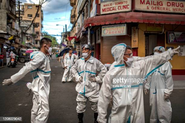 Disinfection workers gather along a street at a suburban area on March 23, 2020 in San Juan, Metro Manila, Philippines. The Philippine government has...
