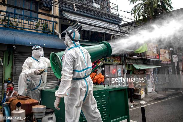 Disinfection workers spray disinfectant from a water cannon along a street at a suburban area on March 23 2020 in San Juan Metro Manila Philippines...