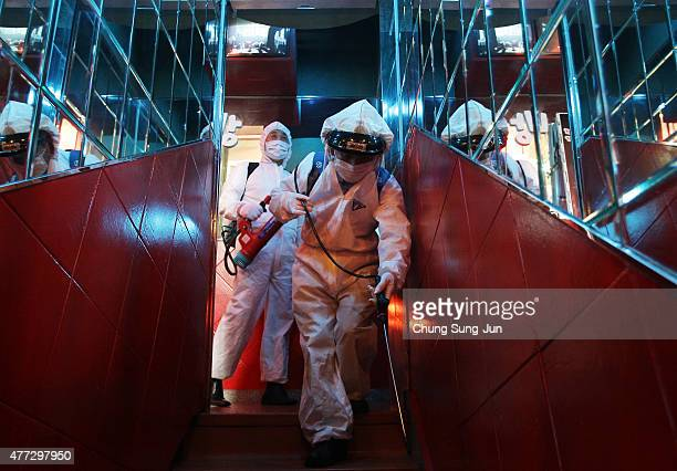 Disinfection workers wearing protective clothing spray antiseptic solution in an karaoke amid rising public concerns over the spread of MERS virus on...