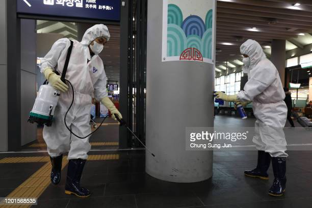 Disinfection workers wearing protective gears spray antiseptic solution in an train terminal amid rising public concerns over the spread of China's...