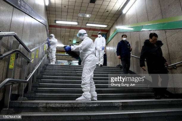 Disinfection workers wearing protective gears spray anti-septic solution against the coronavirus at the subway station on February 21, 2020 in Seoul,...