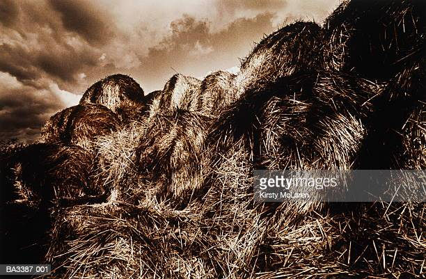 disintegrating pile of hay bales beneath stormy sky, toned b&w - disintegration stock photos and pictures