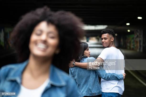 ontrouw man met zijn vriendin kijken naar een ander meisje - vriendje stockfoto's en -beelden