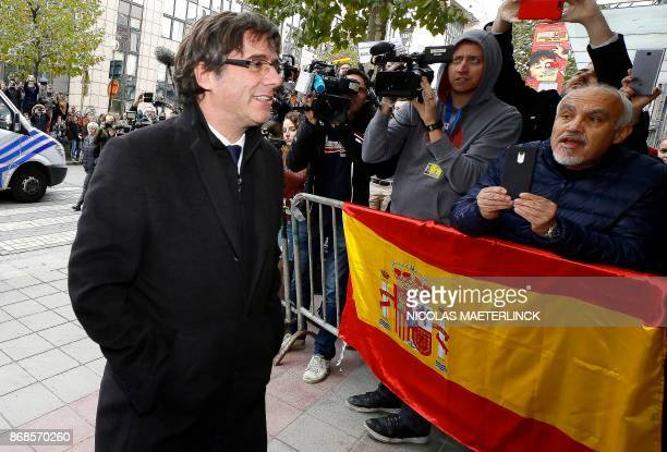 Dismissed Catalonia's leader Carles Puigdemont walks past Spanish flag as he arrives to address a press conference at The Press Club in Brussels on...