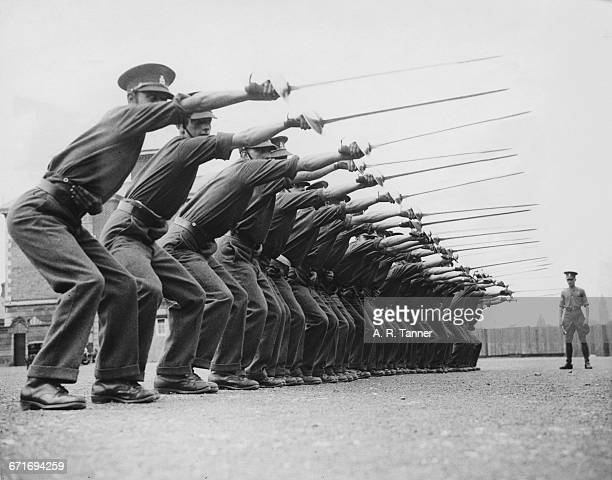 Dismounted troopers of the 4th Queen's Own Hussars in riding position are given drill instruction on how to use the sword at their barracks on 19...