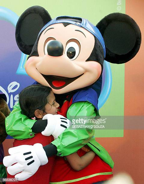 Disney cartoon character Mickey Mouse hugs a girl child at a live performance for kids at a promotional campaign in Mumbai 07 January 2006 'Disney...