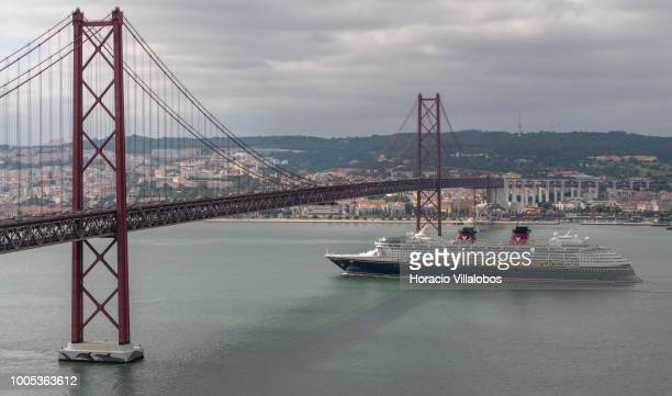 Disney Magic a cruise ship owned and operated by the Disney Cruise Line a subsidiary of The Walt Disney Company sails under 25 de Abril bridge on the...