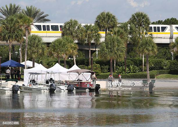 A Disney World monorail passes overhead near the command post of Florida Fish and Wildlife and Orange County Sheriffs Marine Units as they search for...
