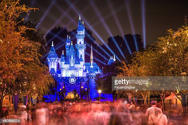 disneyland 60th aniversary castle with people walking - castle stock photos and pictures