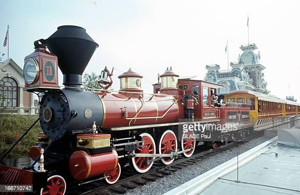 Disneyworld Park In Orlando, Florida. En Floride, au parc de Disneyworld, un train à vapeur, roulant sur des rails dans un décor de ville.