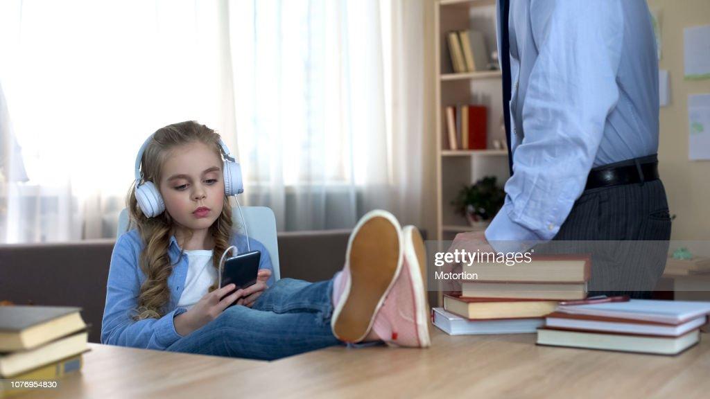 Disobedient girl in headphones listening to music on smartphone, ignoring dad : Stock Photo