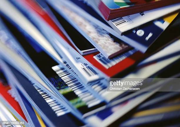 disorderly stack of magazines, extreme close-up on corners with barcodes, full frame - magazine stock pictures, royalty-free photos & images