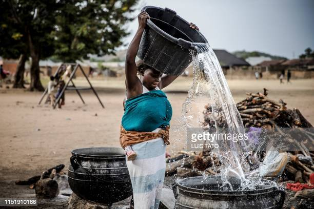 TOPSHOT A displaced Adara woman pours water on a pot before cooking for a group of Adara displaced people at an IDPs refugee camp in Kajuru Kaduna...