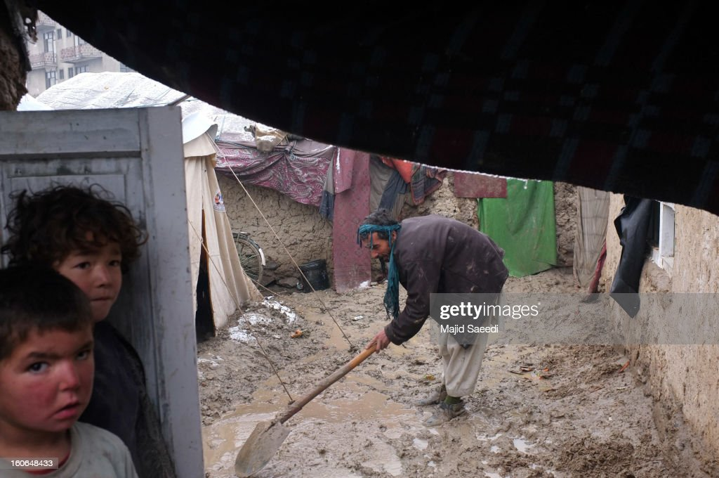 A displaced Afghan man shovels effluent in the heavy rain from outside his family's temporary home at Chamand babrak Camp, on February 3, 2013 in Kabul, Afghanistan. According to the UN refugee agency, Afghanistan's internally displaced population has reached half a million, although the actual figure is believed to be much higher.
