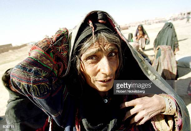 A displaced Afghan woman recently at the Minarets refugee camp with her extended family complains about having to live outdoors without shelter and...