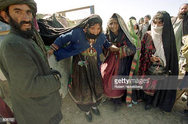 Displaced Afghans disembark from their transport as they arrive at the Minarets refugee camp January 25 2001 in Herat Afghanistan Afghans fleeing the...