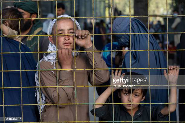 Displaced Afghans look through a fence at a makeshift IDP camp in Share-e-Naw park to various mosques and schools on August 12, 2021 in Kabul,...