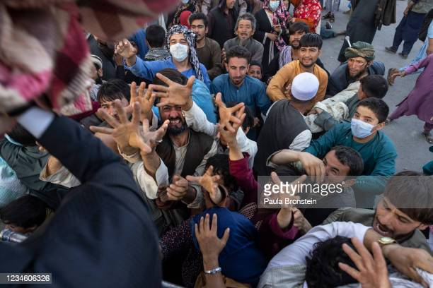 Displaced Afghans reach out for aid from a local Muslim organization at a makeshift IDP camp on August 10, 2021 in Kabul, Afghanistan. The Taliban...