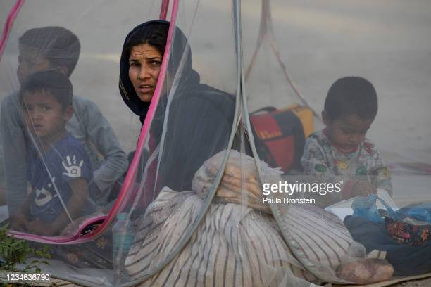 Displaced Afghans sit in a tent at a makeshift IDP camp in Share-e-Naw park to various mosques and schools on August 12, 2021 in Kabul, Afghanistan....