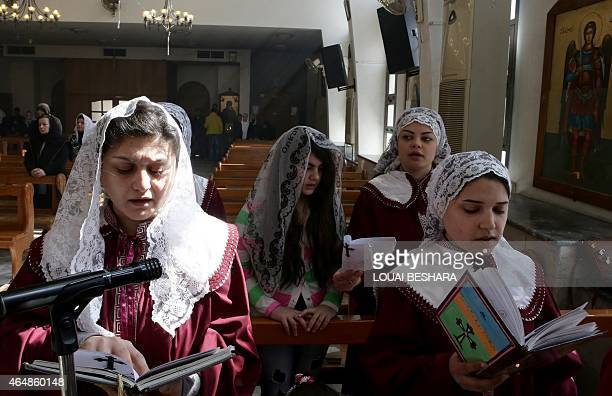Displaced Assyrian women who had fled their hometowns due to Islamic State Group attacks against their communities take part in a prayer at the...